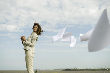 Woman outdoors watching documents caught in wind fly away LANG_EVOIMAGES