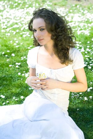 Young woman sitting on the ground, holding flowers, looking sideways at camera LANG_EVOIMAGES