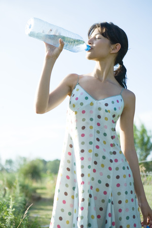 Young woman drinking from bottle of water, eyes closed