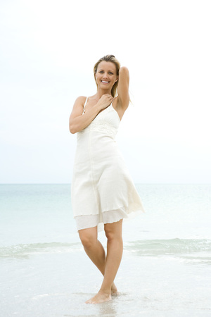 Woman standing at the beach in the surf, smiling at camera