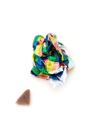 Crumpled candy wrapper and small piece of chocolate LANG_EVOIMAGES