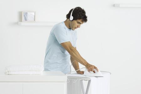 Man ironing towels, listening to headphones