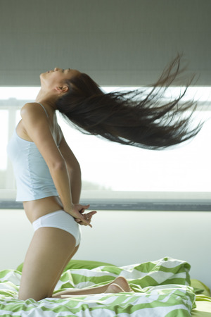 Young woman kneeling on bed tossing hair