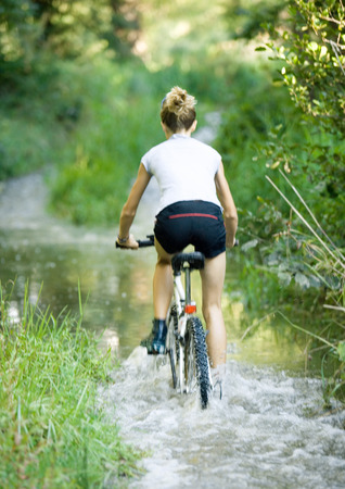overcoming adversity: Girl riding through water on bike, rear view