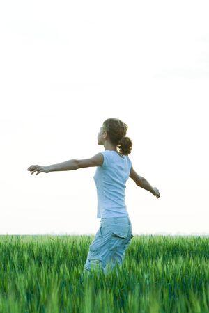 Adolescente de pie en el campo con los brazos extendidos, vista lateral LANG_EVOIMAGES