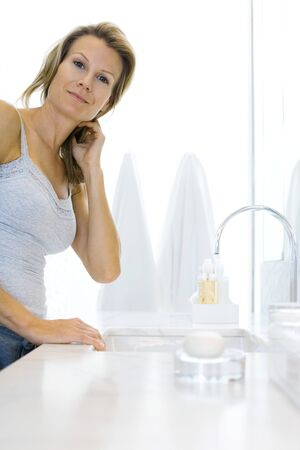 mornings: Woman standing by bathroom sink, smiling at camera