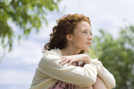Young woman outdoors, looking away in thought LANG_EVOIMAGES