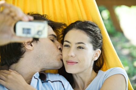 Young couple lying in hammock, taking photo of selves with digital camera
