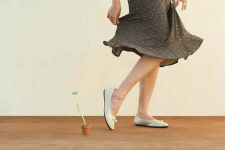 high section: Woman walking past tiny potted plant, holding skirt, cropped view