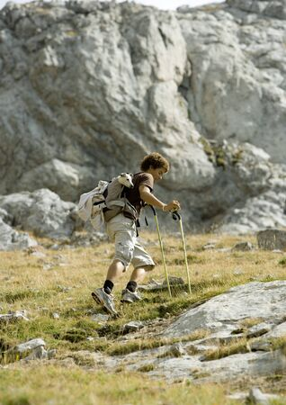 overcoming adversity: Hiker walking through rocky landscape LANG_EVOIMAGES
