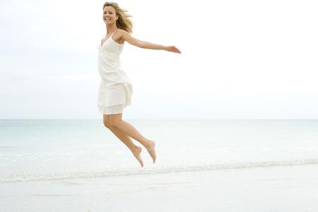 Woman jumping in the air at the beach, smiling at camera
