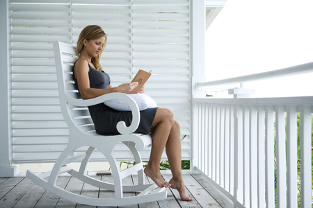 vestidos de epoca: Woman sitting in rocking chair on porch, reading book