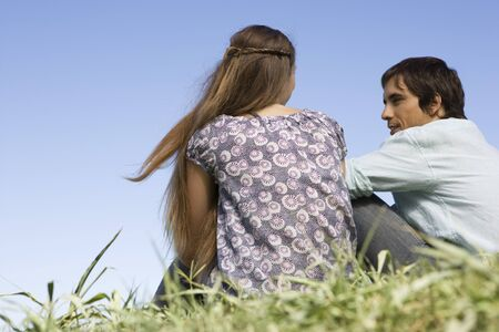 Young couple sitting on grass having conversation