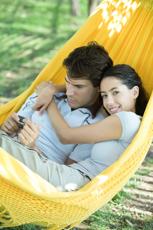 distractions: Young couple lying in hammock, using digital camera, woman smiling at camera LANG_EVOIMAGES