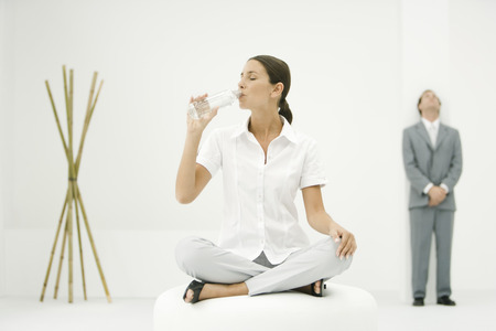 Professional woman sitting on ottoman, drinking from water bottle, businessman and bamboo in background LANG_EVOIMAGES