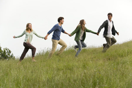 Young adults running on meadow holding hands LANG_EVOIMAGES