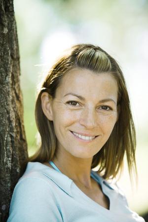 Mujer apoyada en el árbol, sonriendo a la cámara, retrato