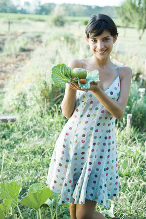Young woman holding up fresh produce in cabbage leaves, smiling at camera