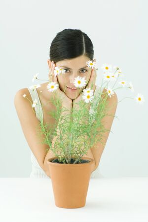 Woman behind potted chamomile, holding head, smiling at camera, portrait