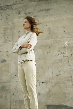 Woman with arms folded, deep in thought, looking away