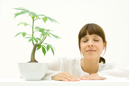 Woman relaxing next to potted plant