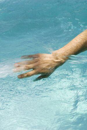Man splashing in pool, cropped view of hand LANG_EVOIMAGES