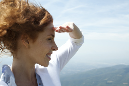 Woman looking at view, shading eyes with hand