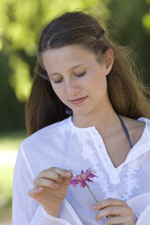 part of me: Young woman plucking petals from flower