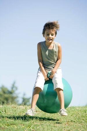 percepción: Little boy outdoors, jumping on ball, full length