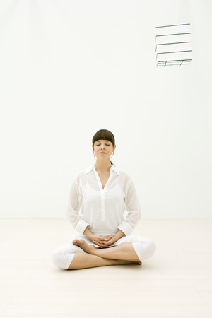 Woman sitting in meditative position, eyes closed