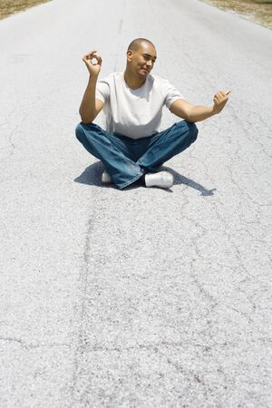 persuading: Hitchhiker sitting in the middle of the road in lotus position, holding one thumb out LANG_EVOIMAGES