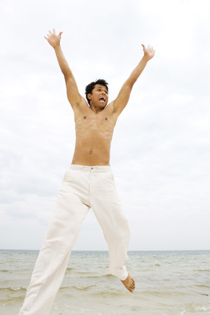 Man jumping in the air at the beach, arms raised, looking away LANG_EVOIMAGES
