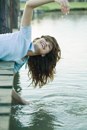 Woman leaning off edge of dock, getting hands wet