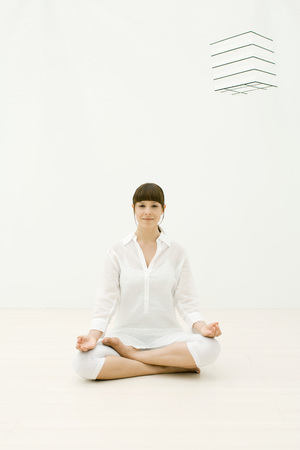 Woman sitting in lotus position, smiling at camera LANG_EVOIMAGES