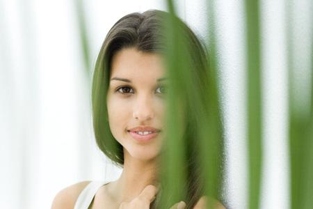 Teen girl, smiling at camera through foliage