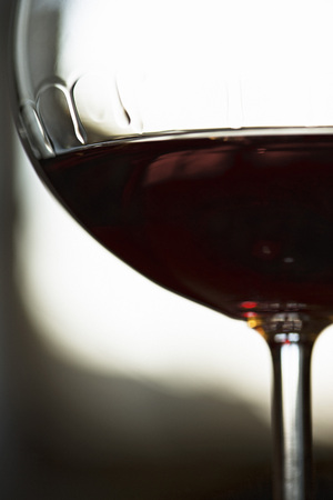 Red wine, bowl of wineglass displaying tears of wine, close-up
