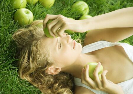 Woman lying in grass, holding apple to forehead LANG_EVOIMAGES