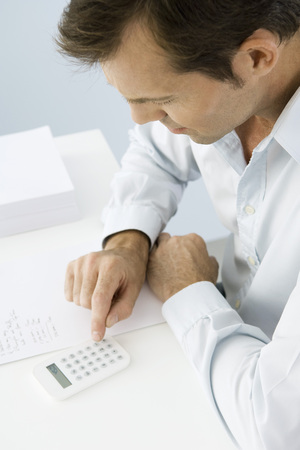 Man using calculator, sitting at table, high angle view LANG_EVOIMAGES