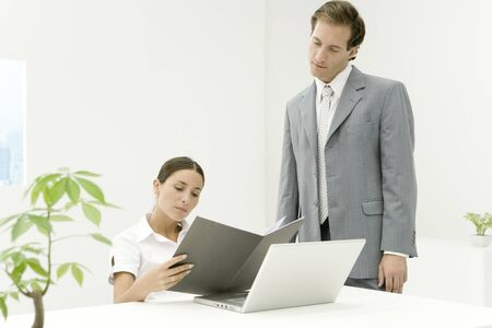 Professionals in office looking at document together