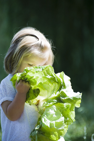 Little girl holding up chard to her face LANG_EVOIMAGES