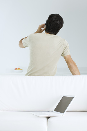 Man talking on cell phone, leaning against sofa with laptop on it, rear view