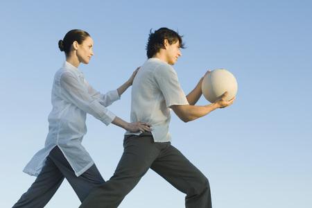 Hombre que sostiene la bola de la aptitud, hombre de colocación de la mujer
