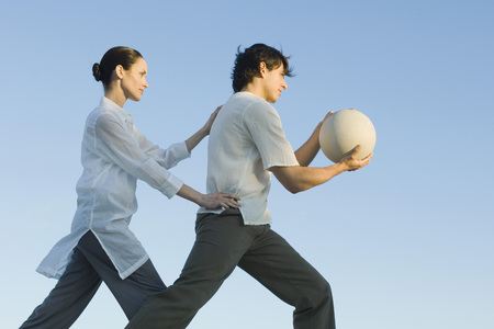 Man holding fitness ball, woman positioning man LANG_EVOIMAGES