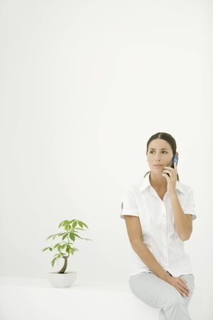 Woman sitting beside potted plant, using cell phone LANG_EVOIMAGES