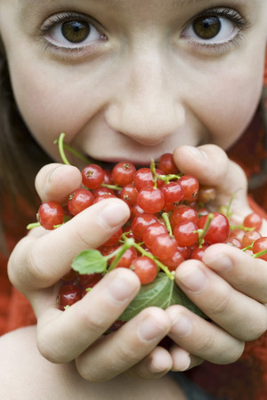 Teenage girl holding up large handful of red currants, close-up LANG_EVOIMAGES