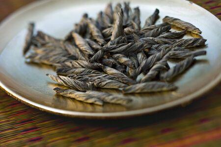 Twists of tea leaves on small plate