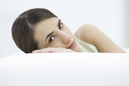 Woman leaning against side of sofa, head resting on hand, smiling at camera LANG_EVOIMAGES