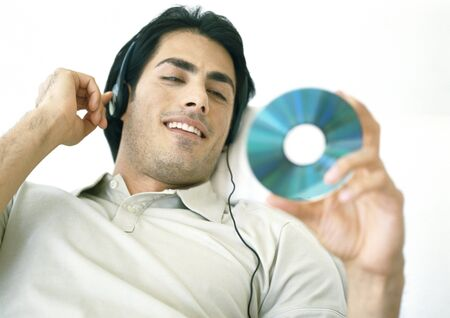 Man listening to headphones, looking at CD LANG_EVOIMAGES