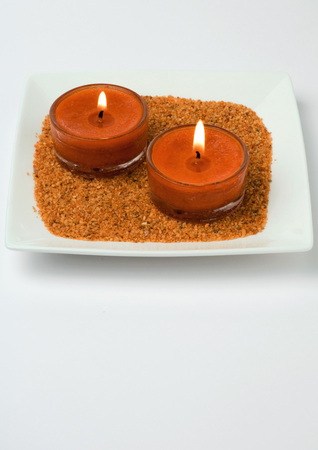 Candles on sand in square dish