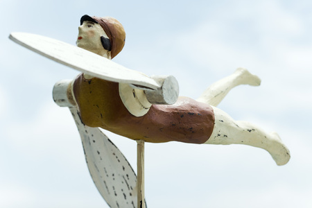 Wooden whirligig carved in the shape of female swimmer